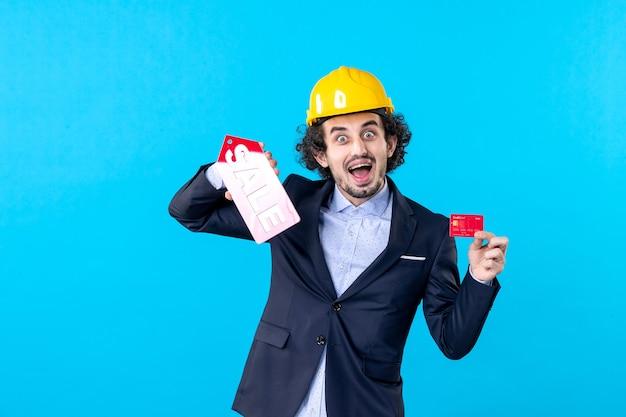 Vue de face homme constructeur tenant une carte bancaire et vente écrit sur fond bleu travail entreprise architecture constructeur bâtiment travail argent
