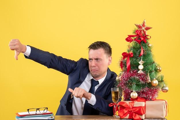 Vue de face de l'homme en costume faisant le pouce vers le bas signe assis à la table près de l'arbre de noël et des cadeaux sur jaune