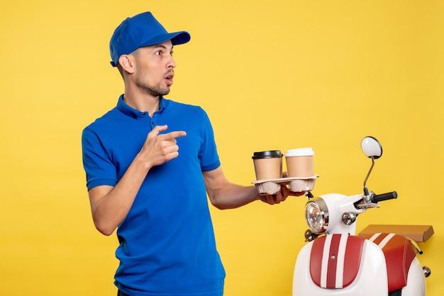 Vue de face homme courrier tenant le café de livraison sur la couleur jaune travail travailleur émotion vélo uniforme