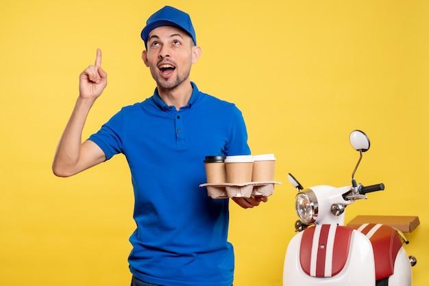Vue de face homme courrier tenant le café de livraison sur la couleur jaune travailleur service travail émotion vélo uniforme