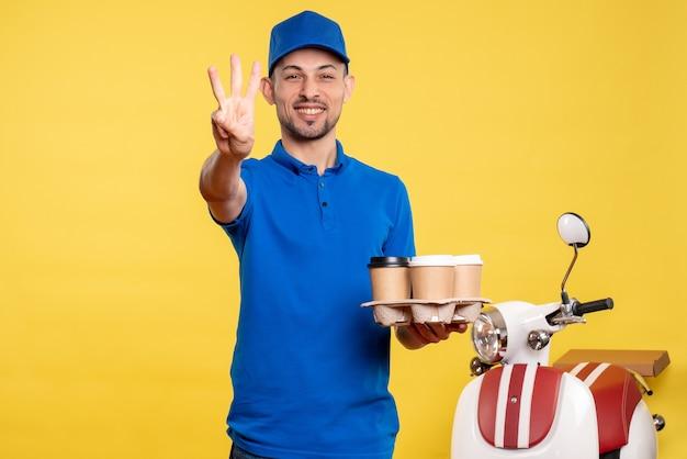 Vue de face homme courrier tenant le café de livraison et souriant sur l'uniforme des émotions de travail de vélo de couleur jaune