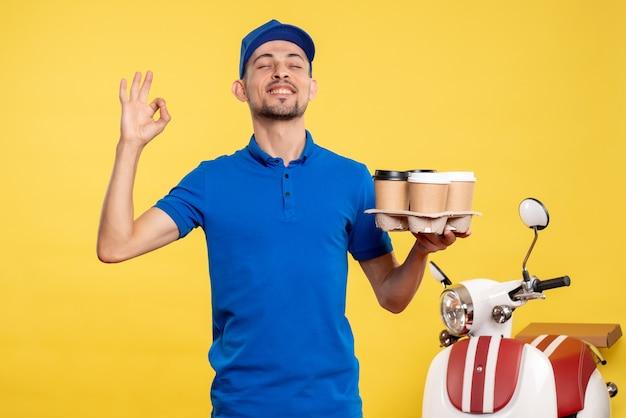 Vue de face homme courrier tenant le café de livraison sur le travail de couleur jaune travail de service de travail de vélo uniforme de livraison