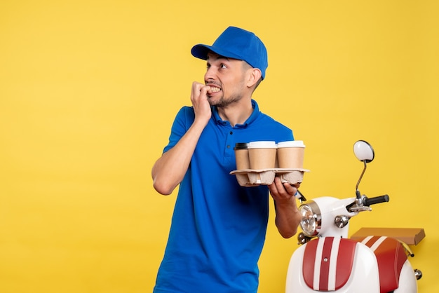 Vue de face homme courrier tenant le café de livraison sur le travail de couleur jaune travail travail travailleur vélo de livraison