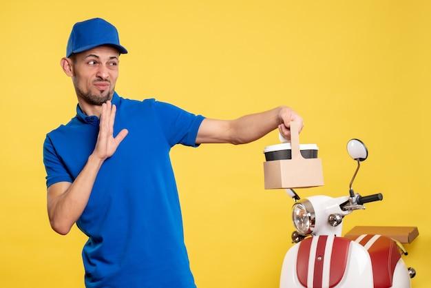 Vue de face homme courrier tenant le café de livraison sur le travail de service d'emploi uniforme de travailleur de couleur jaune