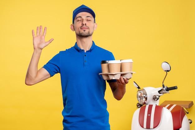 Vue de face homme courrier tenant le café de livraison sur le travail de service de travail de couleur jaune travail de vélo uniforme