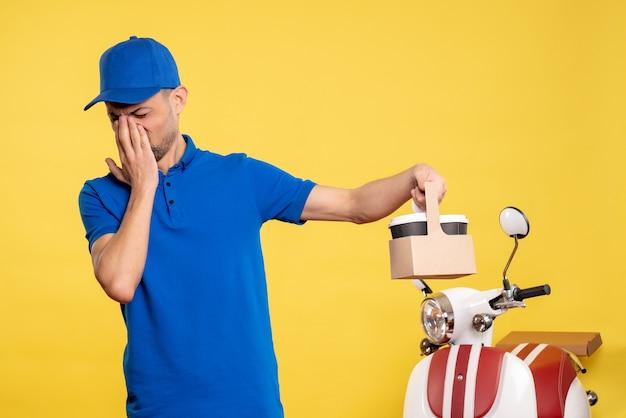 Vue de face homme courrier tenant le café de livraison sur le travail uniforme de travail de travail de vélo de couleur jaune