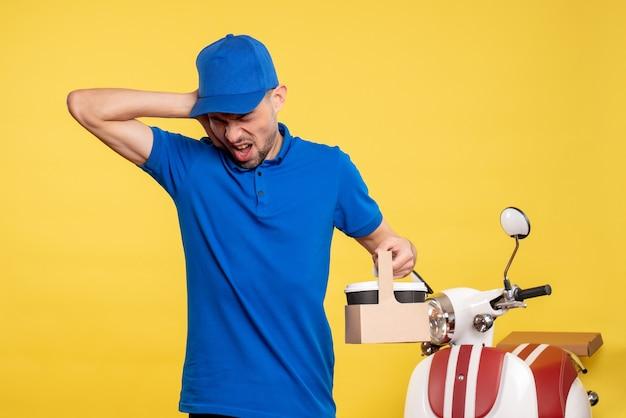 Vue de face homme courrier tenant le café de livraison sur le travail de vélo de service uniforme de travailleur de couleur jaune