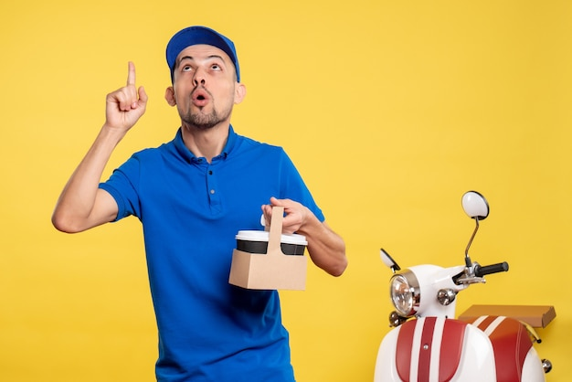 Vue de face homme courrier tenant le café de livraison sur le travail de vélo de travail uniforme de travail de couleur jaune