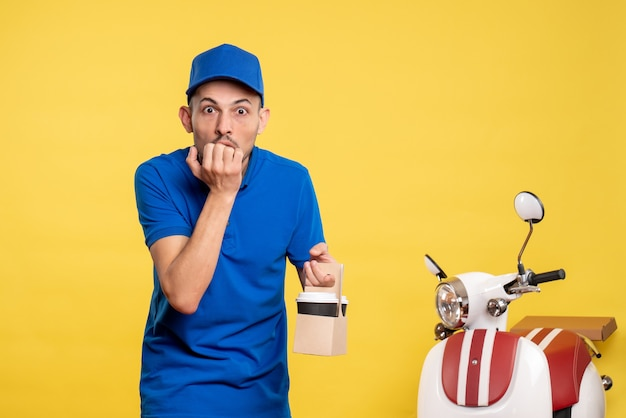 Vue de face homme courrier tenant le café de livraison sur le vélo de service de travail uniforme de travailleur de couleur jaune