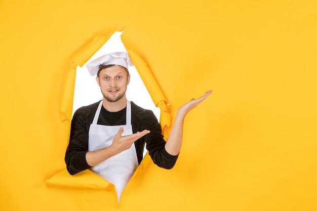Vue de face homme cuisinier en cape blanche et casquette sur une cuisine déchirée jaune travail photo couleur nourriture cuisine