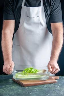 Vue de face homme cuisinier tenant la plaque avec du céleri sur mur sombre salade de régime alimentaire photo couleur santé alimentaire