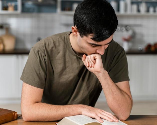 Vue de face de l'homme dans la cuisine la lecture de la bible