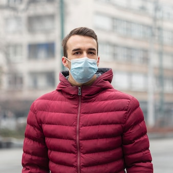 Vue de face de l'homme dans la ville portant un masque médical