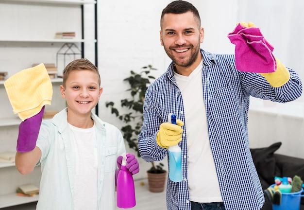 Vue de face de l'homme et du garçon posant pendant le nettoyage de la maison