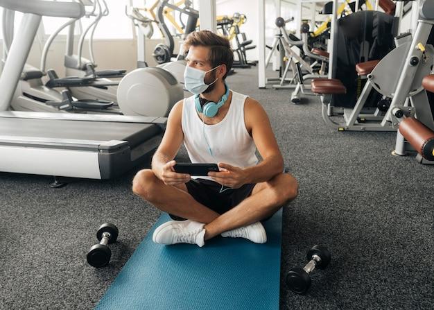 Vue de face de l'homme avec des écouteurs et un masque médical tenant le smartphone dans la salle de sport