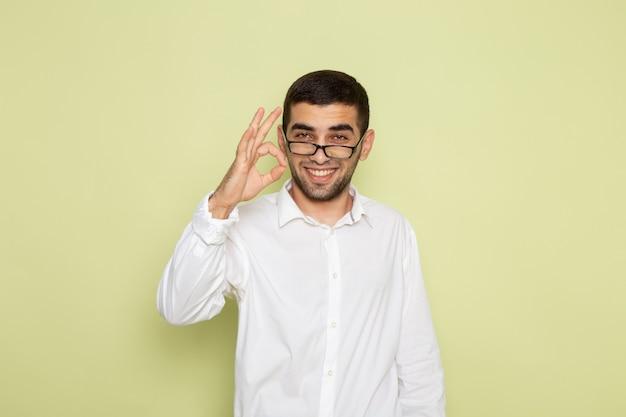 Vue de face de l'homme employé de bureau en chemise blanche souriant et posant sur le bureau vert clair travailleur de bureau travail travail mâle