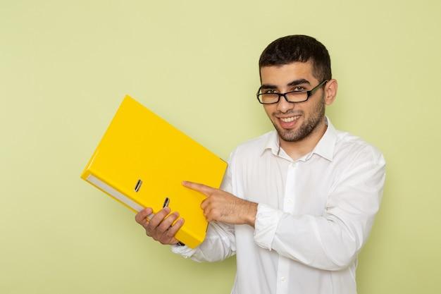 Vue de face de l'homme employé de bureau en chemise blanche tenant un fichier jaune sur le mur vert clair