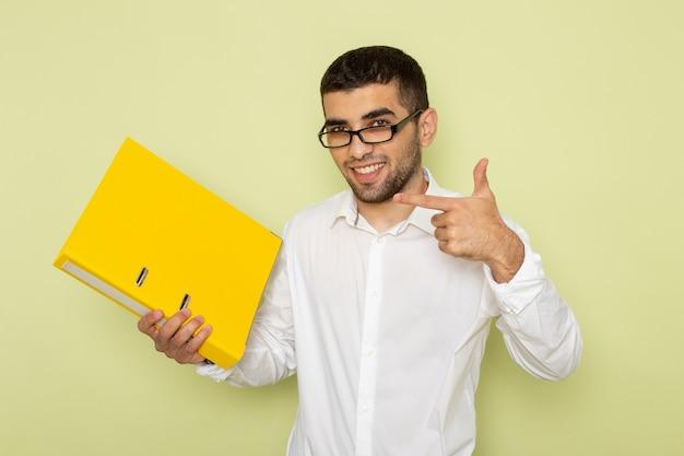 Vue de face de l'homme employé de bureau en chemise blanche tenant des fichiers jaunes avec sourire sur le mur vert