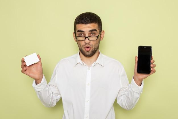 Vue de face de l'homme employé de bureau en chemise blanche tenant le téléphone et la carte sur le mur vert