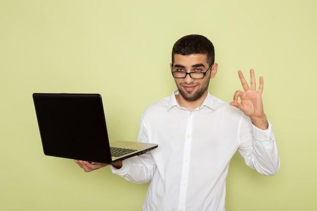 Vue de face de l'homme employé de bureau en chemise blanche tenant et utilisant un ordinateur portable sur le mur vert