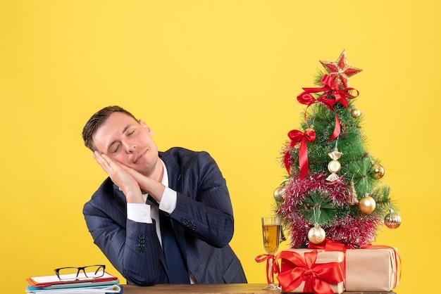 Vue de face de l'homme endormi assis à la table près de l'arbre de noël et des cadeaux sur jaune