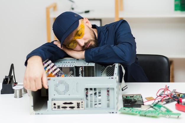 Vue de face homme endormi pendant la réparation d'un ordinateur