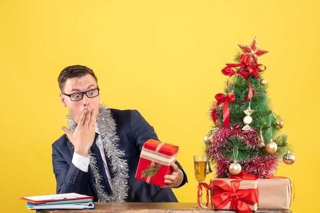 Vue de face homme étonné en regardant son cadeau assis à la table près de l'arbre de noël et présente sur fond jaune