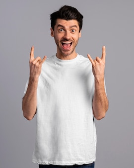 Vue de face de l'homme excité faisant le signe du rock and roll