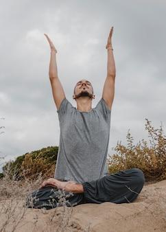 Vue de face de l'homme à l'extérieur pratiquant le yoga