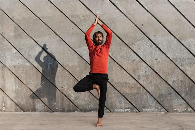 Vue de face de l'homme faisant du yoga à l'extérieur
