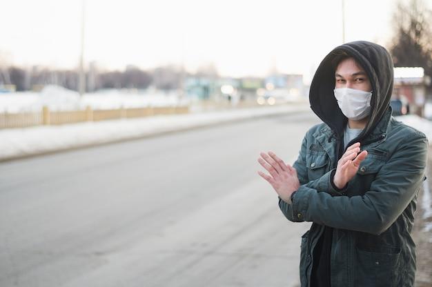 Vue de face de l'homme faisant signe x avec les bras tout en portant un masque médical à l'extérieur