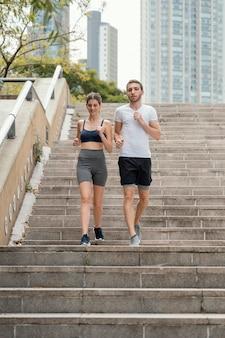 Vue de face de l'homme et de la femme exerçant sur les étapes