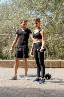 Vue de face de l'homme et de la femme à l'extérieur ensemble exerçant avec des haltères