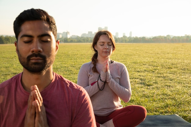 Vue de face de l'homme et de la femme méditant à l'extérieur sur des tapis de yoga