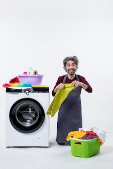 Vue de face homme de femme de ménage heureux debout sur le genou tenant une serviette sur fond blanc