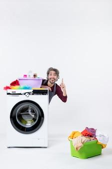 Vue de face homme de femme de ménage en tablier assis derrière le panier à linge lave-linge sur fond blanc