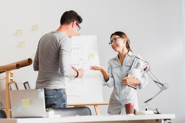 Vue de face homme et femme parlant d'un schéma d'entreprise