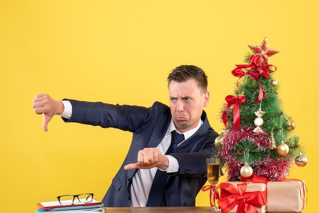 Vue de face de l'homme hargneux faisant le pouce vers le bas signe assis à la table près de l'arbre de noël et cadeaux sur jaune