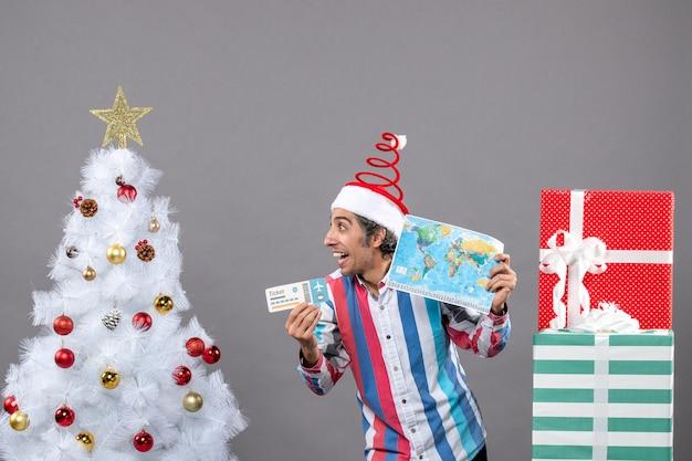Vue de face homme heureux avec bonnet de noel printemps spirale tenant la carte du monde et billet de voyage à droite
