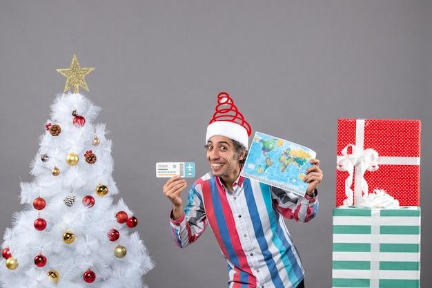 Vue de face homme heureux avec bonnet de noel printemps en spirale tenant carte du monde et billet de voyage