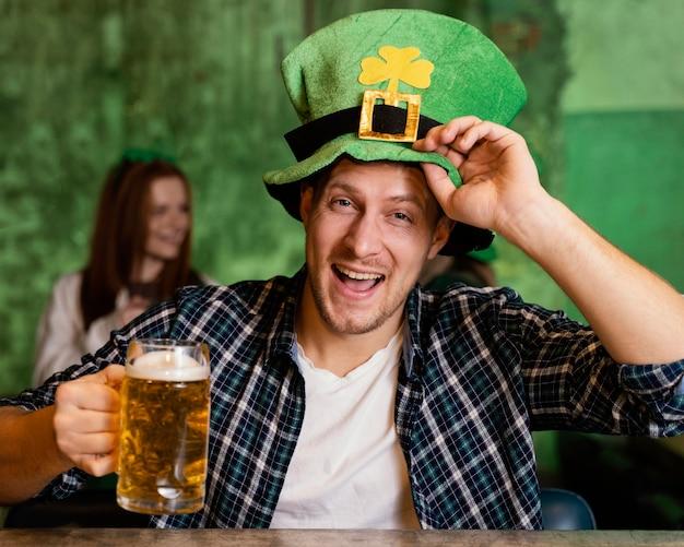 Vue de face de l'homme heureux avec chapeau célébrant st. jour de patrick avec boisson