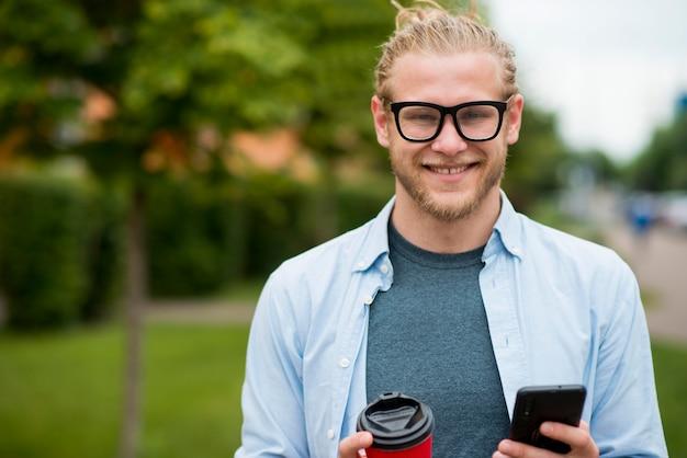 Vue de face de l'homme heureux à l'extérieur avec smartphone et tasse