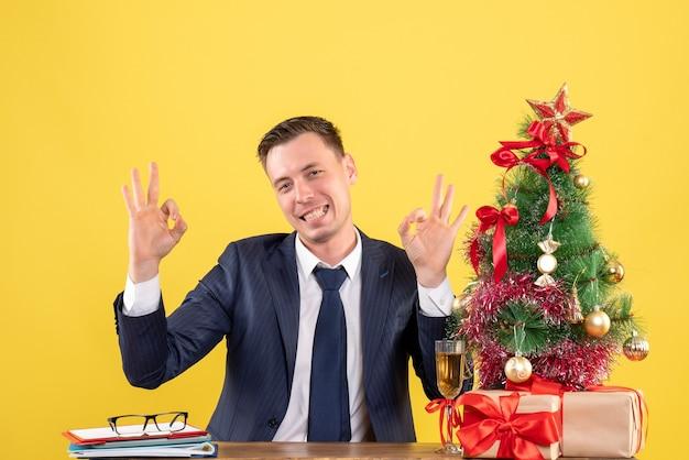Vue de face de l'homme heureux faisant signe okey avec les mains assis à la table près de l'arbre de noël et présente sur jaune