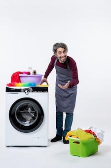 Vue de face homme heureux mettant la main sur un panier à linge lave-linge sur le sol