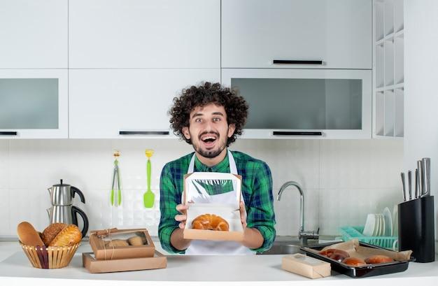 Vue de face d'un homme heureux montrant une pâtisserie fraîchement préparée dans une petite boîte dans la cuisine blanche