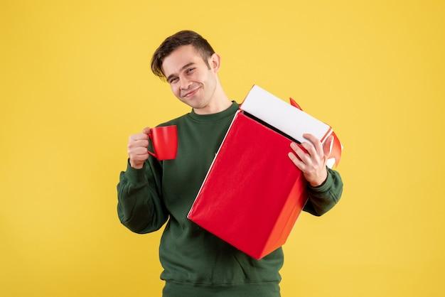 Vue de face homme heureux avec pull vert tenant gros cadeau et tasse rouge debout sur jaune