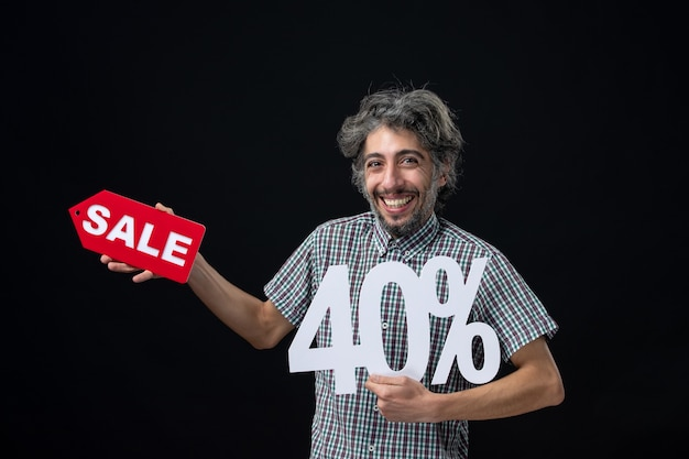 Vue de face d'un homme heureux tenant un signe de marque et de vente sur un mur noir