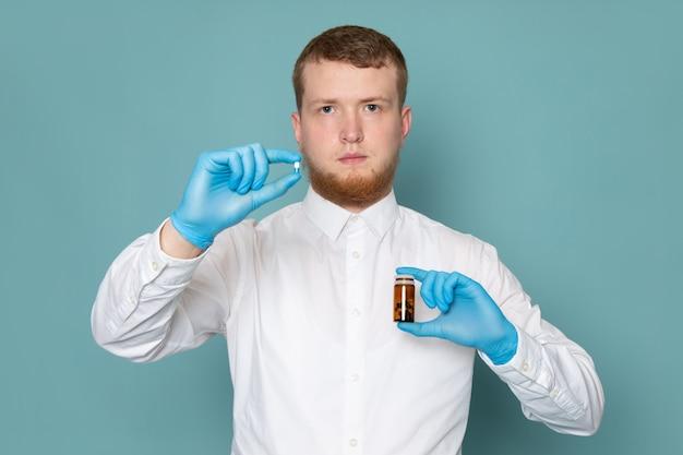 Une vue de face homme jeune en t-shirt blanc tenant des pilules sur le sol bleu