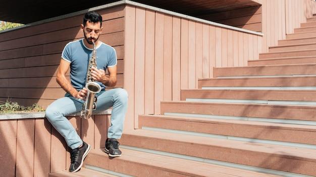 Vue de face de l'homme jouant le concept de saxophone