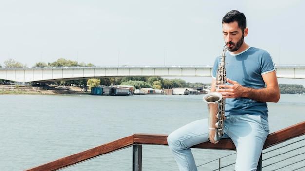 Vue de face de l'homme jouant du saxophone